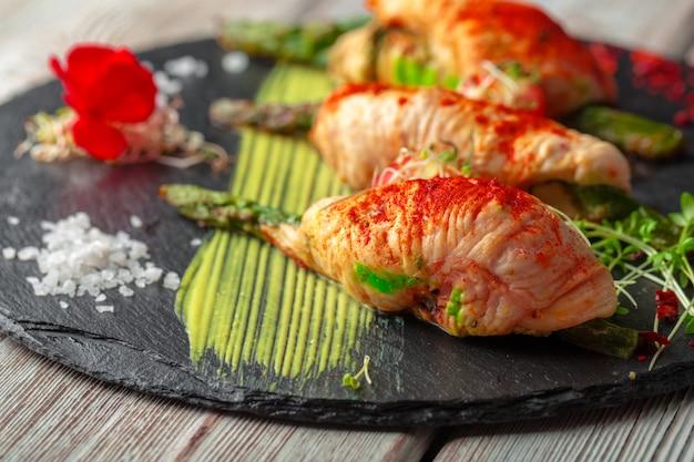 Espargos enrolados com fatias de carne de frango servidas no prato escuro