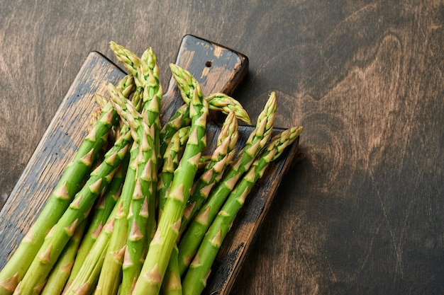Espargos. monte de aspargos verdes frescos prontos para cozinhar em fundo preto de madeira velho