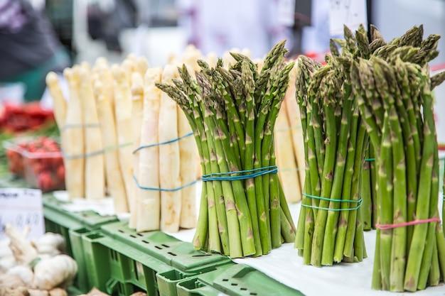 Espargos. pacotes frescos de espargos brancos e verdes no mercado.