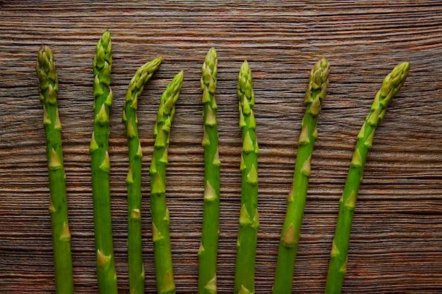 Espargos vegetais crus em uma linha em madeira envelhecida