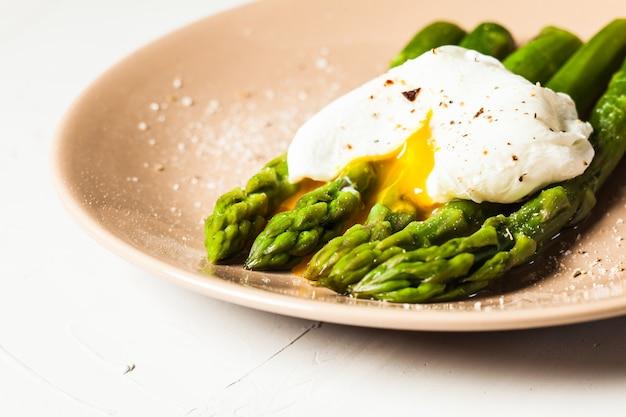 Espargos verdes cozidos com ovo escalfado, com sal e especiarias