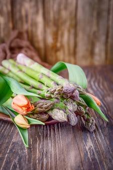 Espargos verdes e tulipas em uma madeira