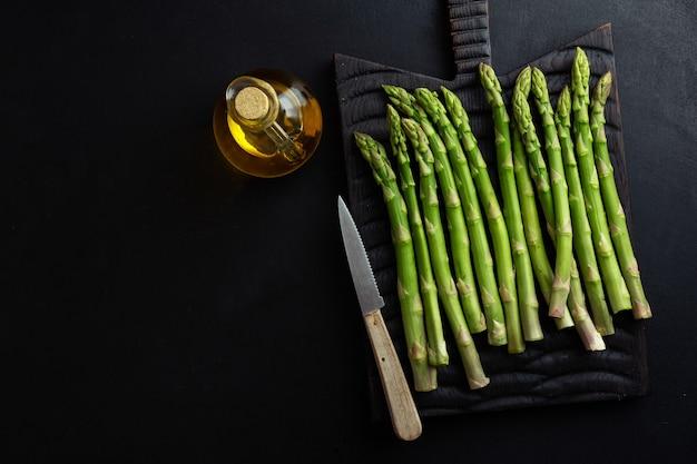 Espargos verdes em superfície escura prontos para cozinhar