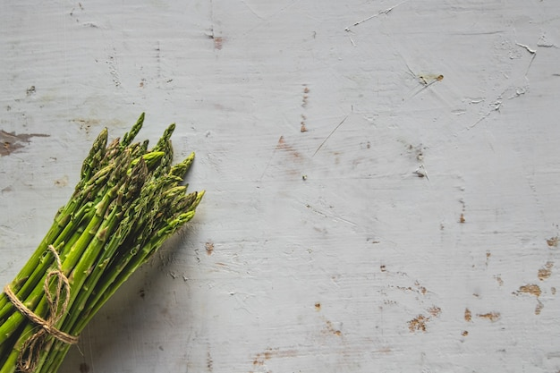 Espargos verdes frescos da primavera em um fundo de madeira. temporada de espargos