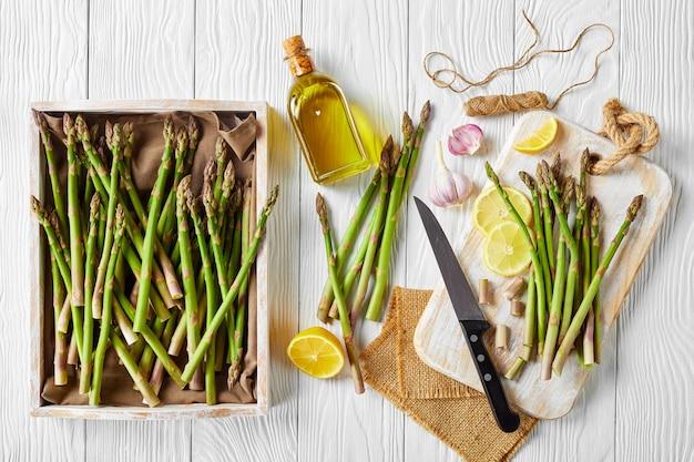 Espargos verdes frescos em uma caixa de madeira rústica e em uma tábua de cortar com faca, rodelas de limão e garrafa de azeite de oliva