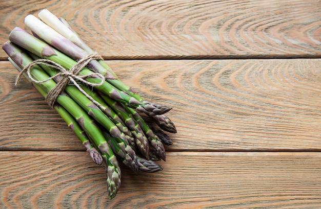 Espargos verdes frescos na velha mesa de madeira. postura plana