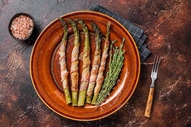 Espargos verdes grelhados embrulhados com bacon em um prato. fundo escuro. vista do topo.