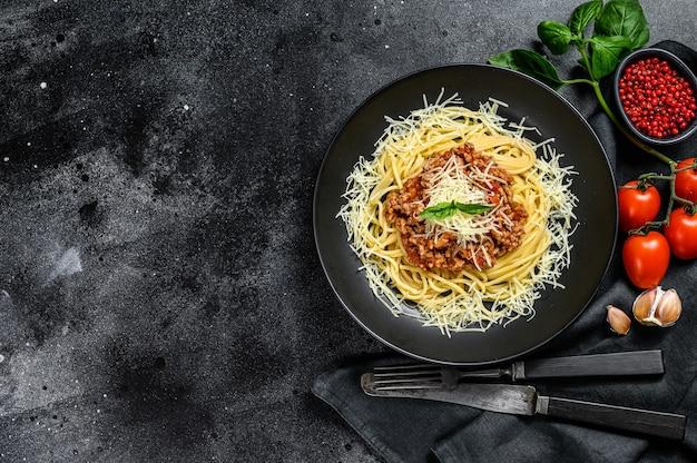 Esparguete à bolonhesa com tomate e carne picada, queijo parmesão e manjericão. fundo preto