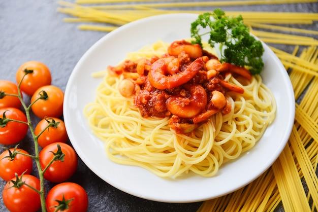 Esparguete à bolonhesa massas italianas com camarão camarão servido no prato branco com salsa de tomate no restaurante comida italiana e menu
