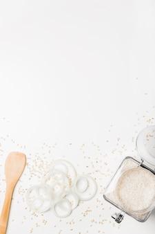 Espátula; anéis de cebola e pote de arroz na superfície branca