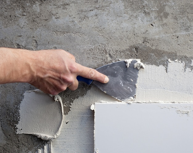 Espátula de espátula construção no trabalho de telha com argamassa