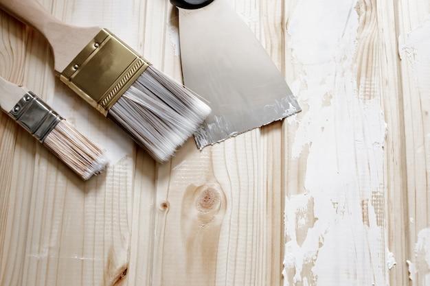 Espátula e escovas para aplicação de massa de vidraceiro na madeira