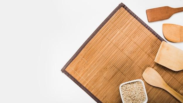 Espátulas de madeira e tigela de arroz cru no placemat contra fundo branco
