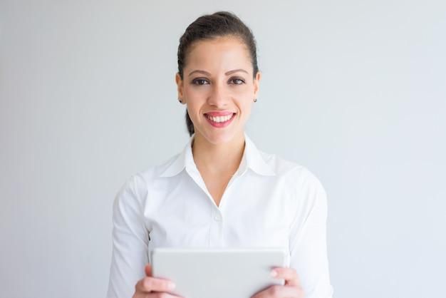 Especialista de negócio bem sucedido feminino feliz olhando para a câmera e usando o tablet.