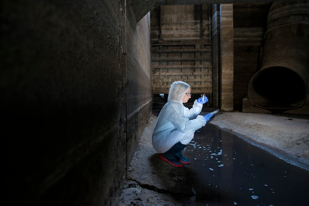 Especialista ecologista ou biotecnologista dentro do esgoto, colhendo amostras de águas residuais para experimentos e análises.