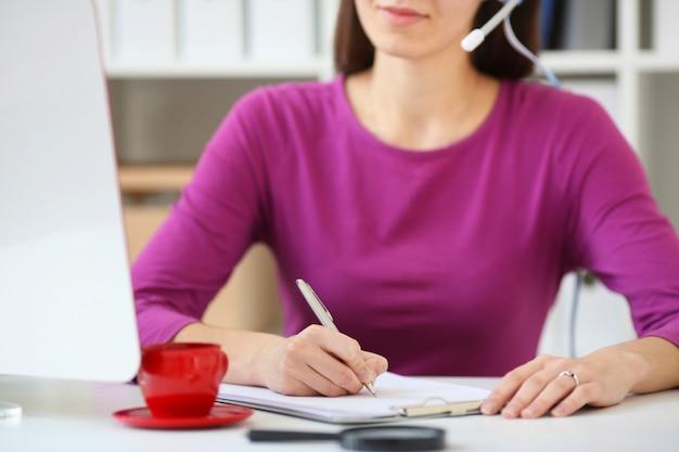 Especialista em call center mulher recebe pedidos por telefone e escreve em um notebook, com profundidade de campo