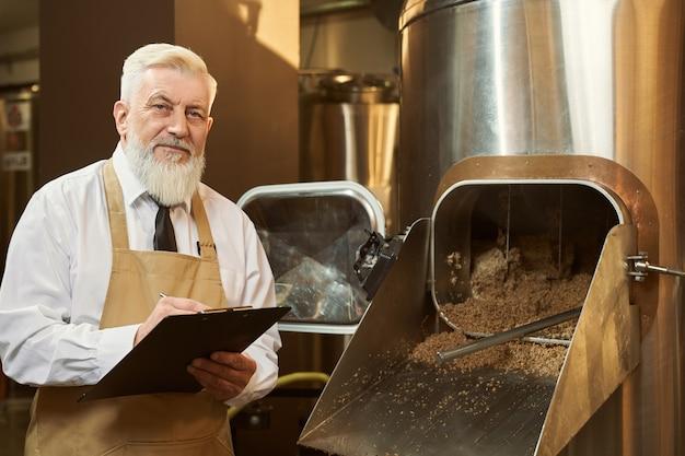 Especialista em cervejaria em pé perto de equipamentos, segurando a pasta
