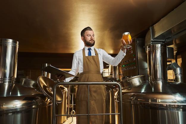 Especialista em cervejaria inspecionando cerveja, segurando o copo