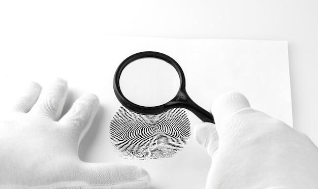 Especialista em criminologia através de uma lupa olhando para uma impressão digital.
