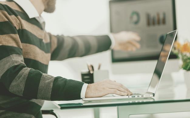 Especialista em finanças trabalhando em laptop com gráficos financeiros e