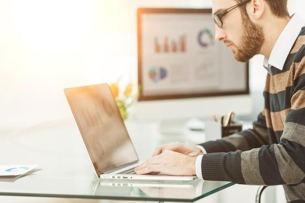 Especialista em finanças trabalhando em um laptop com gráficos financeiros e esquemas de marketing