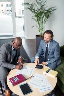 Especialista em impostos. vista superior de um especialista em impostos de cabelos grisalhos consultando seu cliente constante de pele escura