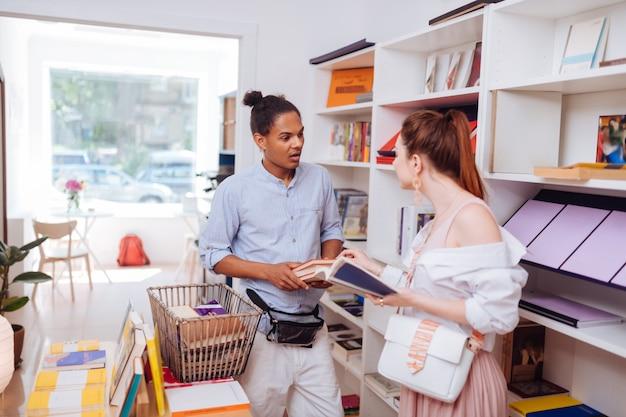 Especialista em livros. garota de cabelos compridos atenta em pé em semi-posição e conversando com um homem de pele escura