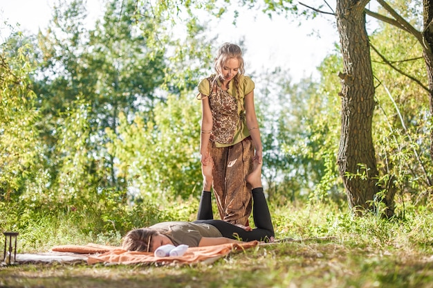 Especialista em massagem demonstra métodos de massagem refrescantes na floresta.