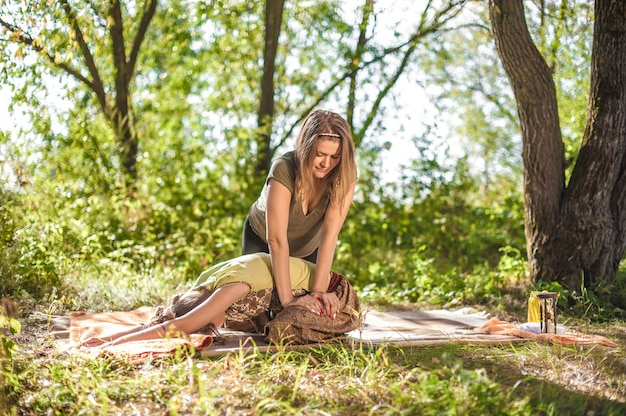 Especialista em massagem demonstra métodos de massagem refrescantes na grama da floresta.