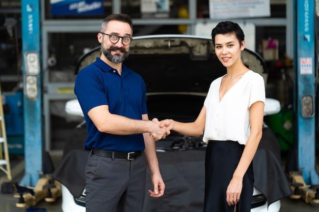 Especialista em mecânico apertando a mão de um cliente satisfeito e trabalhando na garagem de uma estação de manutenção de conserto de automóveis. satisfação no atendimento.