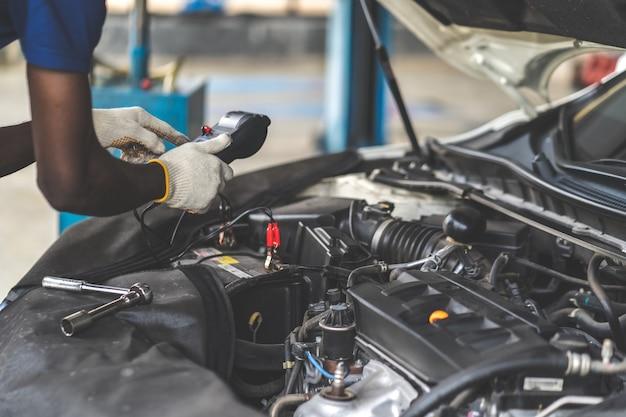 Especialista em mecânico atuando em oficina mecânica. inspeção da bateria. carro mecânico masculino preto, verificando o voltímetro do testador de capacidade da bateria.