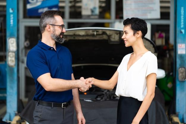 Especialista em mecânico cumprimentando cliente satisfeito e trabalhando em oficina de estação de manutenção de conserto de automóveis