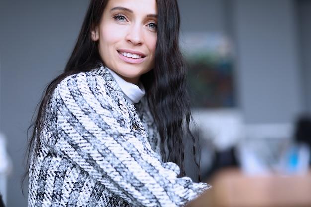 Especialista em mulher de negócios jovem sorrindo no local de trabalho