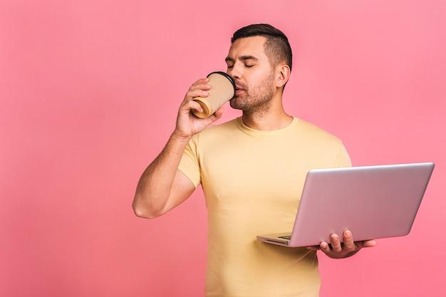 Especialista em negócios confiável. homem bonito jovem confiante casual segurando laptop e sorrindo enquanto. beber café para viagem.