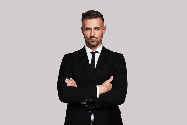 Especialista em negócios. jovem bonito em terno completo, de braços cruzados e olhando para a câmera em pé contra um fundo cinza