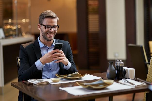 Especialista em negócios masculino sorrindo enquanto segura o telefone com as duas mãos na frente do rosto na mesa do restaurante