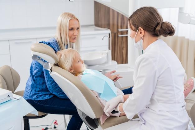 Especialista em pediatria pediátrica, examinando os resultados do exame oral da menina com a mãe.
