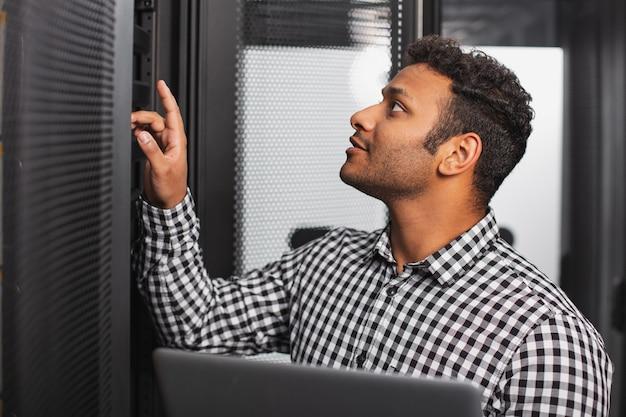 Especialista em tecnologia. cara de ti positiva usando laptop e examinando a sala do servidor