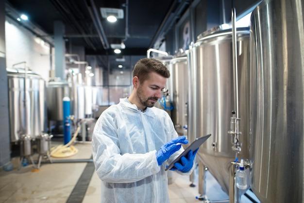 Especialista em tecnologia usando computador tablet em linha de produção de fábrica de alimentos