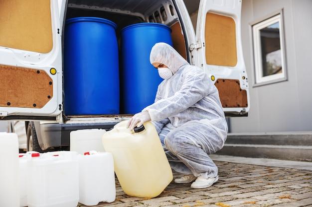 Especialista em trajes anti-risco, preparando-se para a limpeza e desinfecção de células epidêmicas de coronavírus, pandemia mundial de risco à saúde.