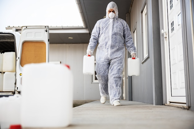 Especialista em trajes anti-risco, preparando-se para a limpeza e desinfecção de células epidêmicas de coronavírus