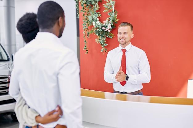 Especialista em vendas caucasiano sorridente dando as boas-vindas aos clientes no showroom de carros