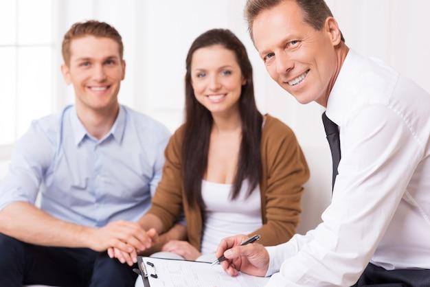 Especialista financeiro confiável. homem maduro confiante de camisa e gravata, olhando para a câmera e sorrindo, enquanto o casal está sentado no fundo e sorrindo