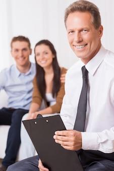 Especialista financeiro confiável. homem maduro confiante de camisa e gravata, segurando a prancheta e olhando para a câmera, enquanto o casal está sentado no fundo e sorrindo