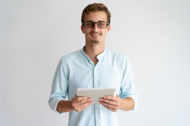 Especialista masculina considerável entusiasmado alegre que trabalha com tabuleta e que olha a câmera.