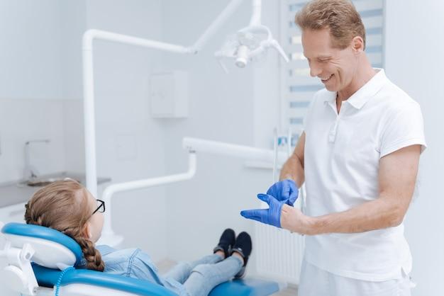 Especialista proeminente bonito e amigável usando uniforme profissional para garantir que tudo esteja limpo e esterilizado para o procedimento