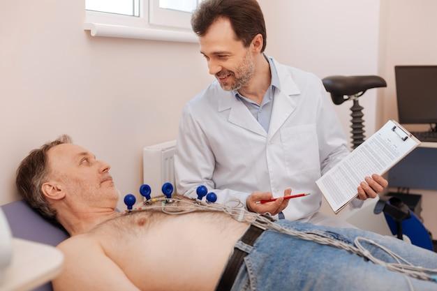 Especialista qualificado, entusiasmado e emocional, mostrando a um homem os resultados de seus testes e explicando-lhe tendências positivas antes de prescrever um tratamento adicional