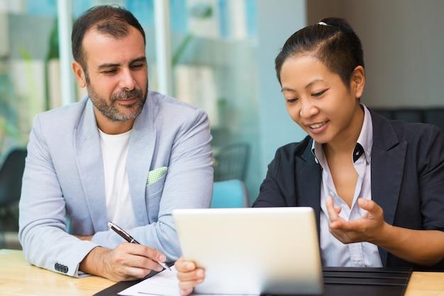 Especialistas em marketing latino e asiático positivos sentados juntos