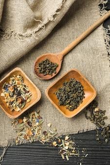 Especiarias à base de plantas na tigela de madeira e colher sobre o saco