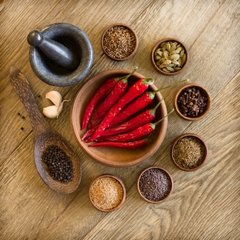 Especiarias, alho e pimenta vermelha em bacias de madeira